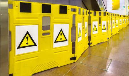 느낌표가있는 노란색 모바일 장벽을주의 깊게 살펴보고주의를 기울여주십시오. 위험 할 수 있습니다.