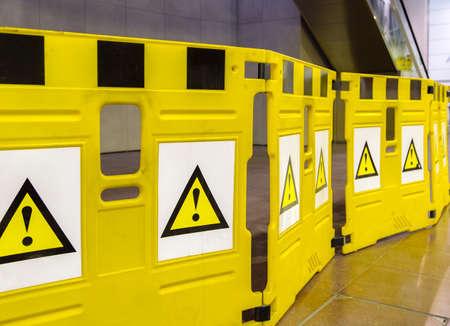 poner atencion: barreras m�viles de color amarillo con signos de admiraci�n, por favor tenga cuidado y prestar atenci�n: existe el peligro en su camino Foto de archivo