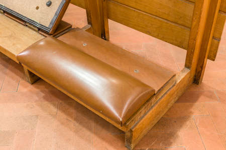 arrepentimiento: reclinatorio con cojín de cuero para apoyar las rodillas de los fieles que rezan en una iglesia católica italiana