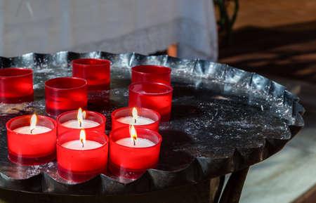 votive: red votive candles arranged on old black iron candlestick, some still burning