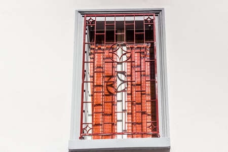 iron curtain: Red iron grating on grey square window with white wood frame and red curtain Stock Photo