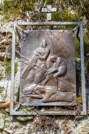 ninth: Bronze picture of the ninth Station of the Cross on a medieval wall in Italian country village: Jesus falls a third time Stock Photo