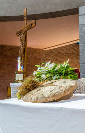 jesus christ communion: bread, grapes and ears of wheat as a symbol of Christian Holy Communion in Italian Catholic Church. Wood statue of the crucifixion of Jesus Christ in the background