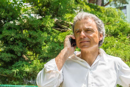 reassuring: Handsome middle-aged man with salt pepper hair dressed with white shirt is talking on mobile phone in city park: he shows a reassuring look