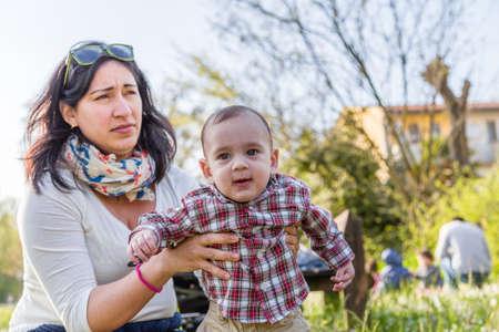 cabello casta�o claro: Lindo beb� de 6 meses de edad con el pelo marr�n claro en camisa a cuadros roja y pantalones de color beige es abrazado y sostenido por su momia hispana