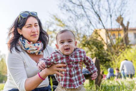 pelo castaño claro: Lindo bebé de 6 meses de edad con el pelo marrón claro en camisa a cuadros roja y pantalones de color beige es abrazado y sostenido por su momia hispana