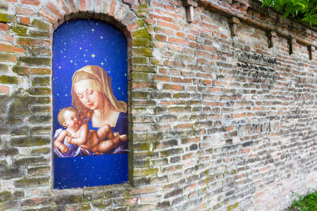 votive: Votive aedicula devoted to the Blessed Virgin Mary with Jesus Christ infant in the brick walls of medieval fortress in Italy