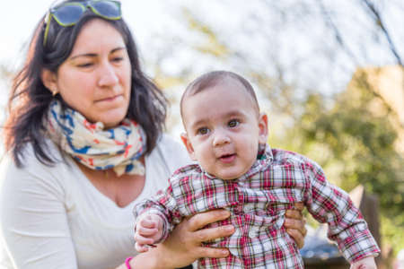 pelo casta�o claro: Cute 6 months old baby with Light brown hair in red checkered shirt and beige pants is embraced and held by his Hispanic mummy Foto de archivo