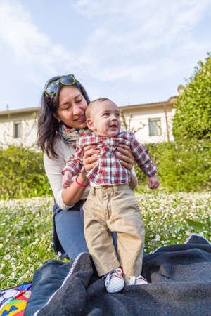 light brown hair: Cute 6 months old baby with Light brown hair in red checkered shirt and beige pants is embraced and held by his smiling Hispanic mummy in a green city park