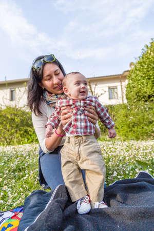 cabello casta�o claro: Lindo beb� 6 meses de edad con el pelo marr�n claro en camisa a cuadros roja y pantalones de color beige es abrazado y sostenido por su sonrisa momia hispana en un parque verde de la ciudad