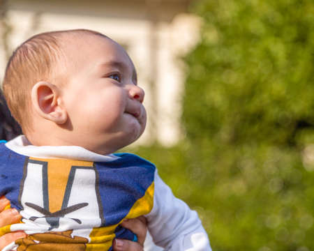 puffing: Cute 6 months old baby with Light brown hair in white, blue and brownish long-sleeved shirt is embraced and held by his mother: he is biting his lips and puffing his cheecks in a funny face Stock Photo