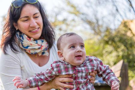 pelo castaño claro: Lindo bebé 6 meses de edad con el pelo marrón claro en camisa a cuadros roja y pantalones de color beige es abrazado y sostenido por su sonrisa momia hispana