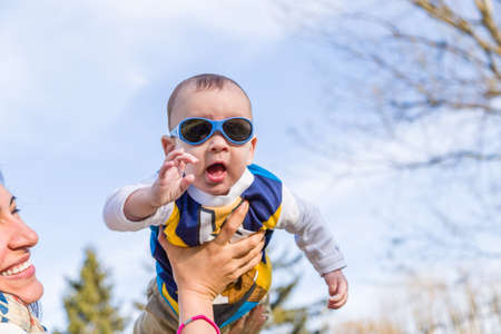 air baby: Cute 6 months old baby with Light brown hair in white, blue and brownish long-sleeved shirt wearing blue googles is raised in the air, embraced and held by his mum
