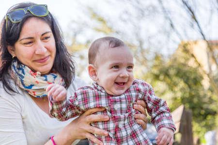 cabello castaño claro: Lindo bebé 6 meses de edad con el pelo marrón claro en camisa a cuadros roja y pantalones de color beige es abrazado y sostenido por su sonrisa momia hispana