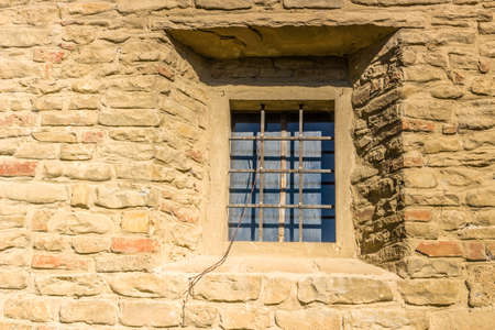 Iron grating window on ancient brick wall of Catholic church in Italian countryside Stock Photo