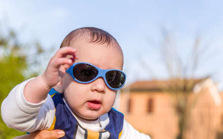 brownish: Cute 6 months old baby with Light brown hair in white, blue and brownish long-sleeved shirt wearing blue googles is embraced and held by his mum Stock Photo