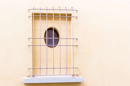 grating: Lilac iron grating window with round hole on vintage wall