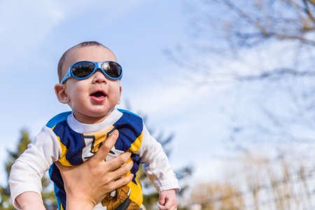 cabello casta�o claro: Lindo beb� 6 meses de edad con el pelo marr�n claro en camisa de manga larga blanca, azul y marr�n que llevaba gafas azules se eleva en el aire, abrazado y sostenido por su madre Foto de archivo