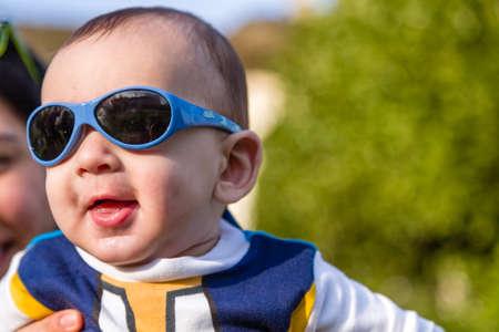 pelo castaño claro: Lindo bebé 6 meses de edad con el pelo marrón claro en camisa de manga larga blanca, azul y marrón que llevaba gafas azules es abrazado y sostenido por su madre: parece muy feliz y sonríe Foto de archivo