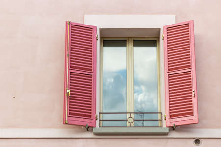 red shutters: Iron grating window with red shutters