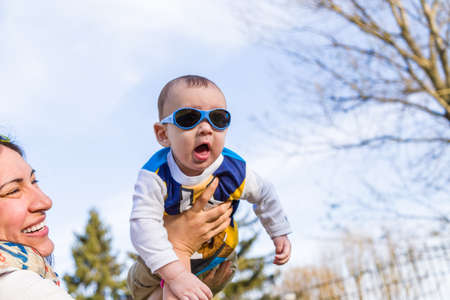 light brown hair: Cute 6 months old baby with Light brown hair in white, blue and brownish long-sleeved shirt wearing blue googles is raised in the air, embraced and held by his mum