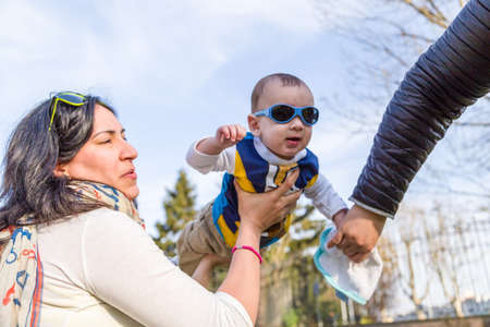 air baby: Cute 6 months old baby with Light brown hair in white, blue and brownish long-sleeved shirt wearing blue googles is raised in the air by her mother and taken in hand by his father