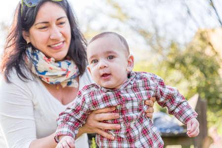 pelo casta�o claro: Lindo beb� 6 meses de edad con el pelo marr�n claro en camisa a cuadros roja y pantalones de color beige es abrazado y sostenido por su sonrisa momia hispana