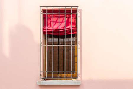 Hierro ventana de reja con la cortina roja Foto de archivo