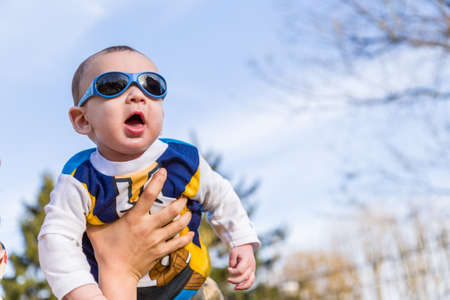 brownish: Cute 6 months old baby with Light brown hair in white, blue and brownish long-sleeved shirt wearing blue googles is raised in the air, embraced and held by his mum