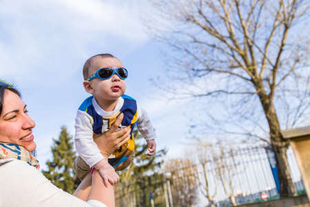 cabello castaño claro: Lindo bebé 6 meses de edad con el pelo marrón claro en camisa de manga larga blanca, azul y marrón que llevaba gafas azules se eleva en el aire, abrazado y sostenido por su madre Foto de archivo