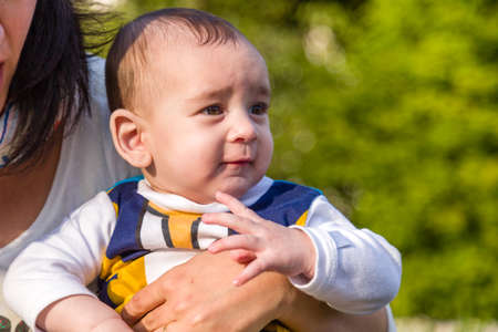 brownish: Cute 6 months old baby with Light brown hair in white, blue and brownish long-sleeved shirt is embraced and held by his mother