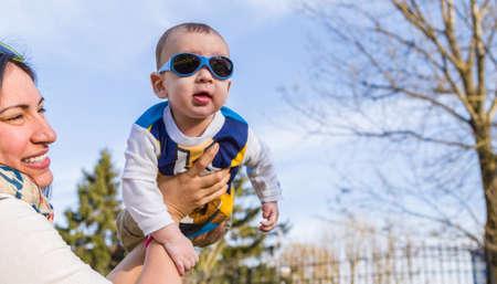 pelo castaño claro: Lindo bebé 6 meses de edad con el pelo marrón claro en camisa de manga larga blanca, azul y marrón que llevaba gafas azules se eleva en el aire, abrazado y sostenido por su madre Foto de archivo