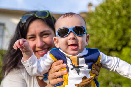light brown hair: Cute 6 months old baby with Light brown hair in white, blue and brownish long-sleeved shirt wearing blue googles is embraced and held by his mum: he seems very happy and smiles