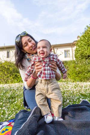 pelo castaño claro: Lindo bebé 6 meses de edad con el pelo marrón claro en camisa a cuadros roja y pantalones de color beige es abrazado y sostenido por su sonrisa momia hispana en un parque verde de la ciudad
