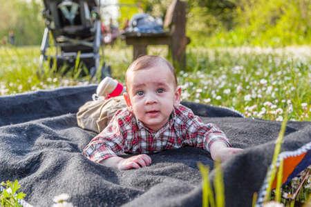 pelo castaño claro: Lindo bebé de 6 meses de edad con el pelo marrón claro con pantalones camisa a cuadros rojos y beige parece curioso pero serena