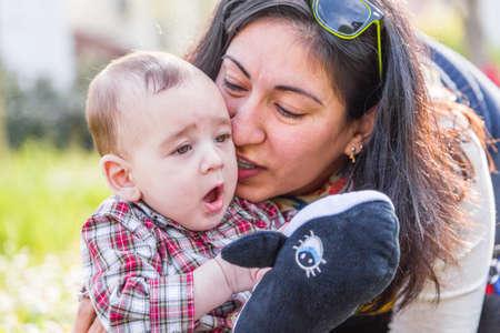 cabello castaño claro: Lindo bebé 6 meses de edad con el pelo marrón claro en pantalones de la camisa a cuadros rojos y beige está escuchando momia hispana