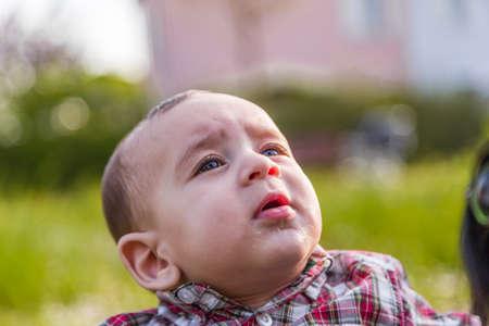 pelo castaño claro: Lindo bebé 6 meses de edad con el pelo marrón claro en camisa a cuadros roja y pantalones de color beige se boquiabierta