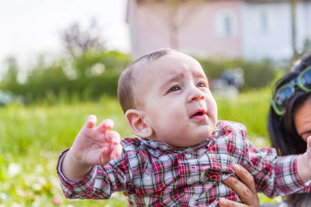 light brown hair: Cute 6 months old baby with Light brown hair in red checkered shirt and beige pants is gaping and looking up while embraced by mother Stock Photo