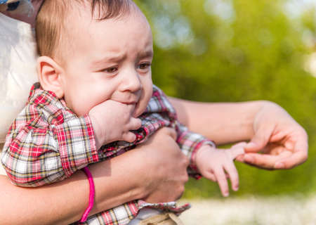 embraced: Cute 6 months old baby with Light brown hair in red checkered shirt and beige pants is biting his fingers while embraced by his Hispanic mother Stock Photo
