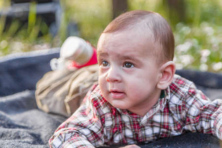 light hair: Cute 6 months old baby with Light brown hair in red checkered shirt and beige pants seems curious but serene