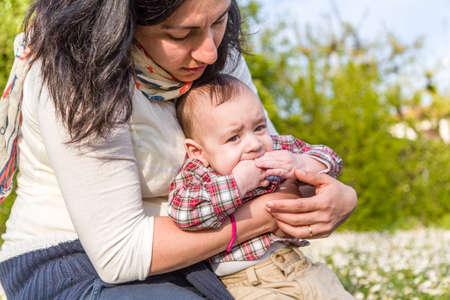 pelo castaño claro: Lindo bebé 6 meses de edad con el pelo marrón claro en camisa a cuadros roja y pantalones beige está mordiendo los dedos mientras abrazado por su madre hispana
