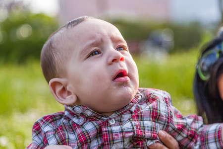 cabello castaño claro: Lindo bebé 6 meses de edad con el pelo marrón claro en pantalones de la camisa a cuadros rojos y beige se boquiabierta y mirando hacia arriba mientras abrazado por la madre Foto de archivo