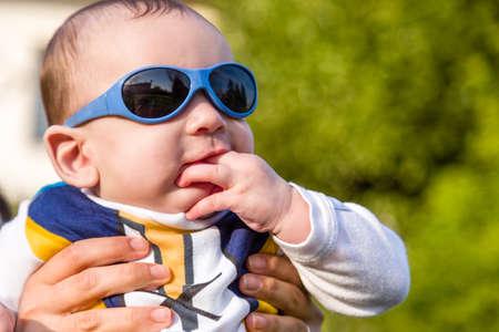 pelo castaño claro: Lindo bebé de 6 meses de edad con el pelo marrón claro en camisa de manga larga blanca, azul y marrón que llevaba gafas azules es abrazado y sostenido por su madre mientras se mordía los dedos