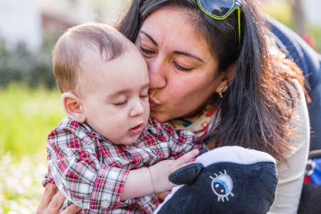 light brown hair: Cute 6 months old baby with Light brown hair in red checkered shirt and beige pants is receiving a kiss from hispanic mummy Stock Photo