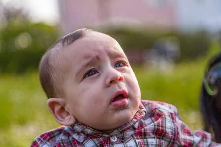 cabello casta�o claro: Lindo beb� 6 meses de edad con el pelo marr�n claro en camisa a cuadros roja y pantalones de color beige se boquiabierta