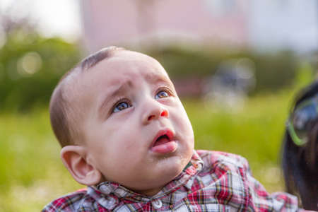 gaping: Cute 6 months old baby with Light brown hair in red checkered shirt and beige pants is gaping Stock Photo