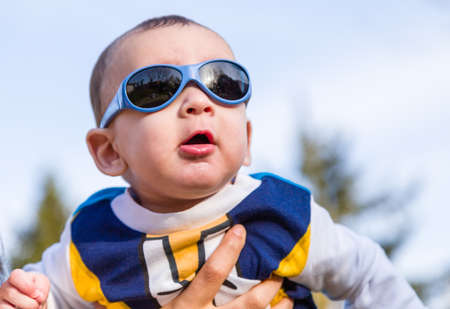 light brown hair: Cute 6 months old baby with Light brown hair in white, blue and brownish long-sleeved shirt wearing blue goggles is embraced and held by his mum
