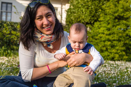 cabello casta�o claro: Lindo beb� 6 meses de edad con el pelo marr�n claro en camisa de manga larga blanca, azul y marr�n es abrazado y sostenido por su madre Foto de archivo
