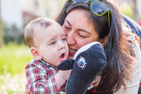 cabello casta�o claro: Lindo beb� 6 meses de edad con el pelo marr�n claro en pantalones de la camisa a cuadros rojos y beige est� escuchando momia hispana