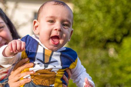 pelo castaño claro: Lindo bebé 6 meses de edad con el pelo marrón claro en camisa de manga larga blanca, azul y marrón es abrazado y sostenido por su madre: parecen muy felices